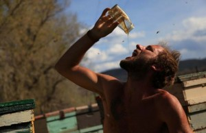 shirtless man drinking honey from a jar