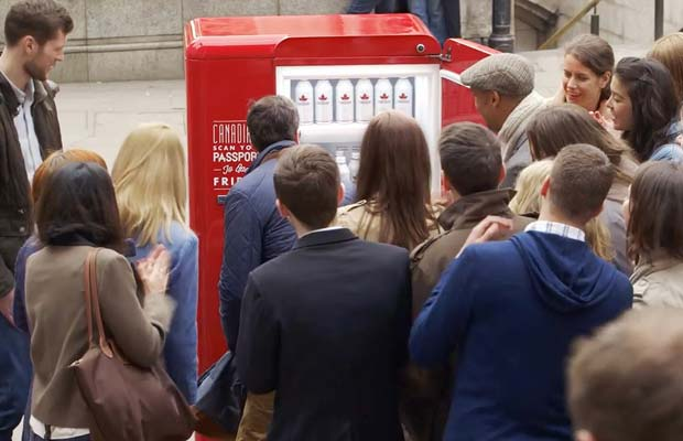 people queuing to fridge with free beer for Canadians
