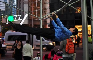 man in suit performing front lever pulls in the city