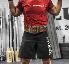 man squating in gym belt
